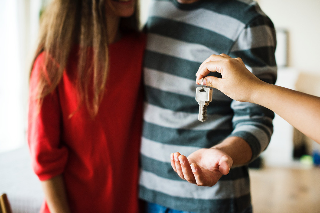 Person giving woman in red shirt and man in striped shirt keys