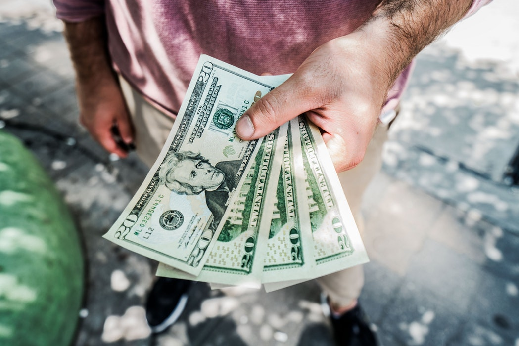 Man in red shirt with hairy arms holding four twenty dollar bills
